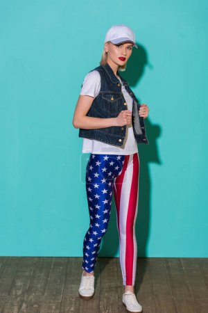 stylish young woman in cap, white shirt, denim jacket and leggings with american flag pattern posing on blue background