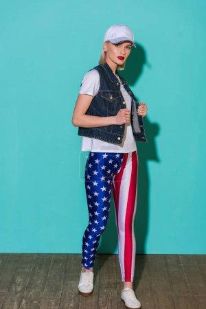Photo pour Élégante jeune femme au chapeau, chemise blanche, veste en Jean et legging avec motif drapeau américain posant sur fond bleu - image libre de droit