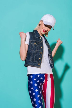 cheerful stylish woman in cap, white shirt, denim jacket and leggings with american flag pattern posing on blue background