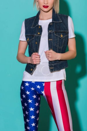 cropped shot of stylish woman in white shirt, denim jacket and leggings with american flag patternon blue backdrop