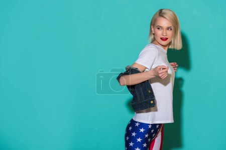 side view of stylish young woman in white shirt, denim jacket and leggings with american flag pattern on blue backdrop