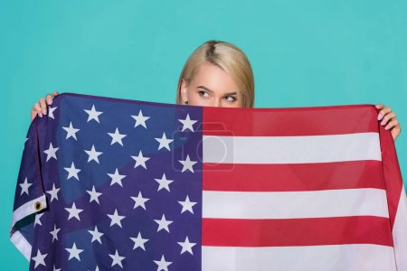 obscured view of woman with american flag looking away on blue backdrop, celebrating 4th july concept