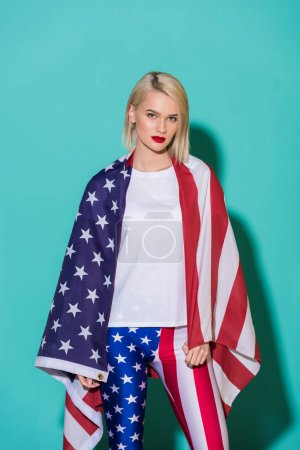 portrait of young woman in white shirt with american flag on blue backdrop, celebrating 4th july concept