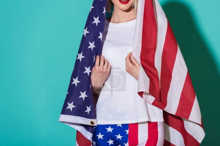 partial view of woman in white shirt with american flag on blue backdrop, celebrating 4th july concept