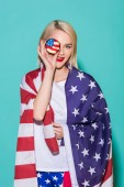 portrait of young woman with american flag and cupcake on blue backdrop, celebrating 4th july concept