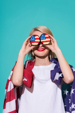 obscured view of smiling woman with american flag and cupcakes on blue backdrop, celebrating 4th july concept