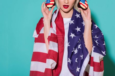 partial view of woman with american flag and cupcakes on blue backdrop, celebrating 4th july concept