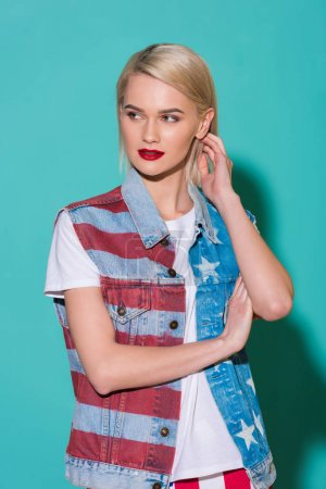 Photo pour Portrait de jeune femme élégante veste en Jean avec motif drapeau américain posant sur fond bleu - image libre de droit