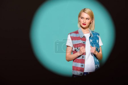 portrait of stylish woman in denim jacket with american flag pattern posing on blue backdrop