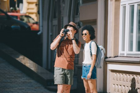 male traveler taking picture on camera and african american girlfriend standing near