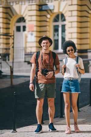 Photo pour Couple de jeunes touristes avec caméra et sacs à dos, debout sur la rue - image libre de droit