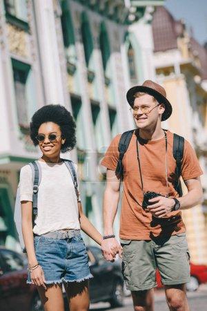 Photo pour Smiling couple multiculturel de voyageurs avec caméra et sacs à dos, tenant par la main de l'autre - image libre de droit