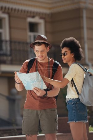 multicultural couple of tourists with map looking for destination