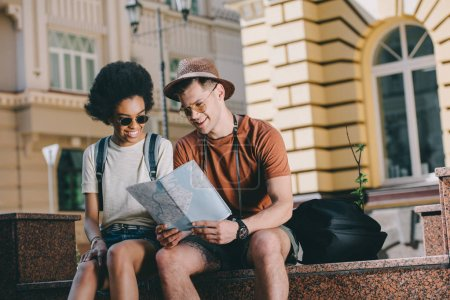 Photo for Smiling interracial couple of tourists with map looking for destination - Royalty Free Image