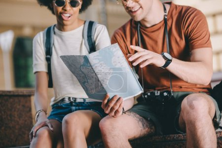 cropped image of couple of travelers sitting with map and looking for destination