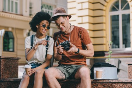 smiling african american female traveler pointing on camera screen to boyfriend