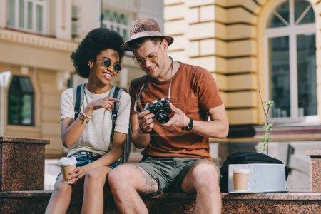 Photo pour Souriant afro-américain voyageur femme pointant sur l'écran de la caméra pour petit ami - image libre de droit