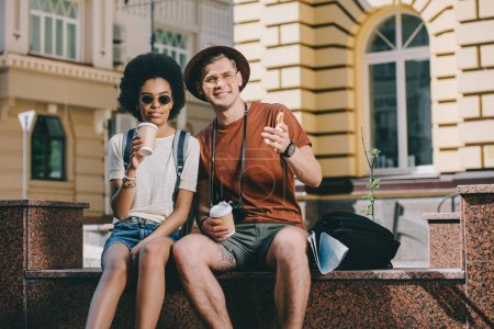 male tourist with paper cup of coffee pointing to african american girlfriend
