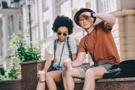Foto de Pareja multicultural de jóvenes turistas sentados con tazas de café - Imagen libre de derechos