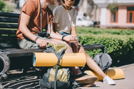Photo for Cropped image of couple of travelers sitting on bench with backpacks and mats - Royalty Free Image