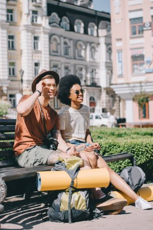 multicultural couple of tourists with backpacks and mats resting on bench