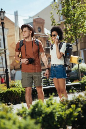 Photo for Male traveler with camera and his girlfriend talking on smartphone - Royalty Free Image