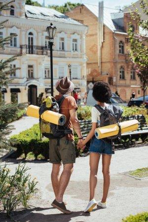 Photo pour Vue arrière du couple de touristes avec sacs à dos et mats tenant par la main de l'autre - image libre de droit
