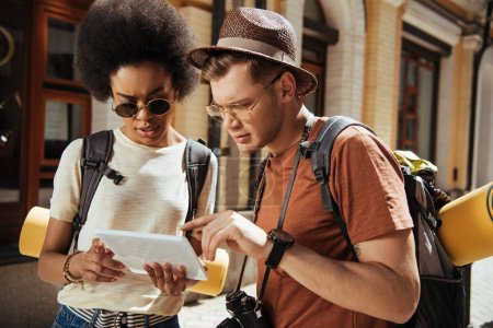 serious multicultural couple of tourists with digital tablet looking for destination