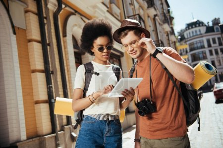 Photo for African american female traveler in sunglasses holding digital tablet and her boyfriend looking for destination - Royalty Free Image