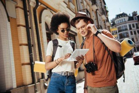 Photo pour Afro-américaine voyageuse en lunettes de soleil tenant tablette numérique et son petit ami à la recherche d'une destination - image libre de droit