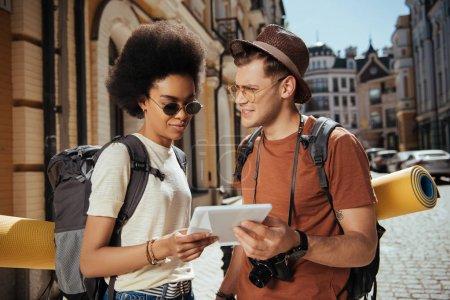 Photo pour Jeune couple multiethnique de touristes avec caméra et tablette numérique - image libre de droit