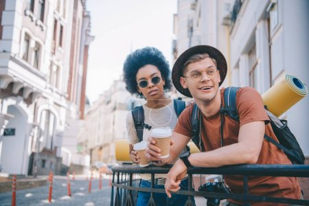 Photo for Multicultural couple of tourists holding coffee cups and looking away - Royalty Free Image