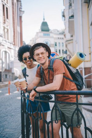 happy young interracial couple of travelers with paper cups of coffee