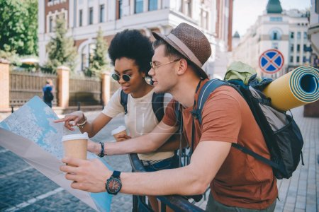 multiethnic couple of young tourists with map and coffee cups