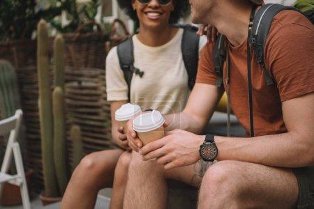 Cropped image du couple assis avec des gobelets jetables de café