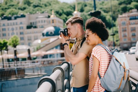 side view of male traveler taking picture on camera and african american girlfriend standing near