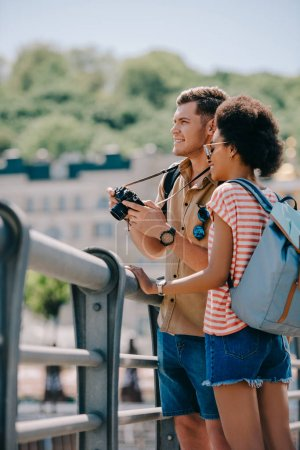Photo for Young male tourist with camera and african american girlfriend - Royalty Free Image