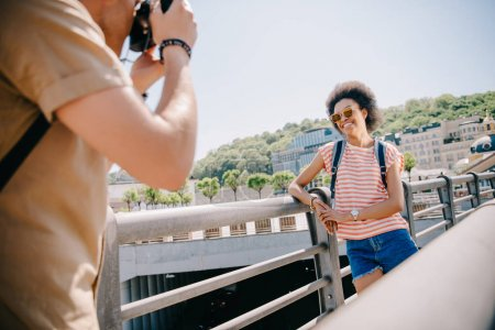 Photo for Cropped image of man taking picture of female tourist in sunglasses on camera - Royalty Free Image