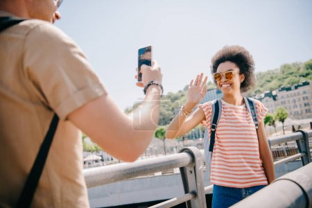 cropped shot of male traveler taking picture of smiling girlfriend waving hand on smartphone