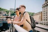 Multicultural heureux couple de touristes avec des tasses à café en regardant vue du pont