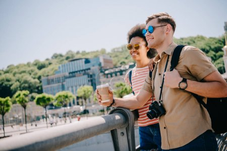 smiling interracial couple of tourists in sunglasses with coffee and camera looking at view from bridge