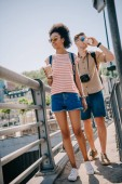 interracial couple of tourists with disposable cups of coffee and camera walking on bridge