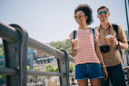 Foto de Vista de ángulo bajo de pareja multiétnica de turistas con las tazas de papel del café y la cámara - Imagen libre de derechos