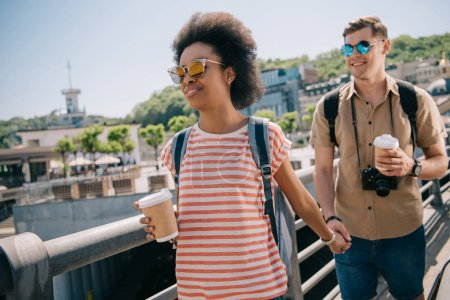 interracial couple of tourists with paper cups of coffee and camera holding hands and walking on bridge