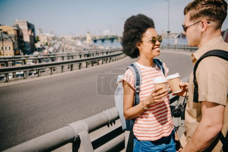 smiling african american female traveler and her boyfriend with paper cups of coffee talking to each other