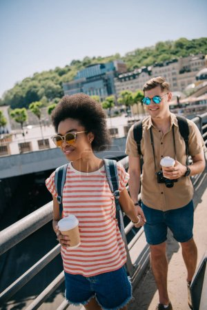 young multicultural couple of tourists with coffee cups and camera walking on bridge