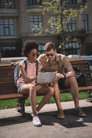 african american female traveler and her boyfriend looking at map and sitting on bench