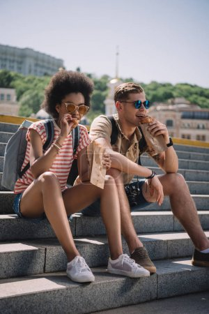 multiethnic couple of travelers sitting on stairs and eating croissants