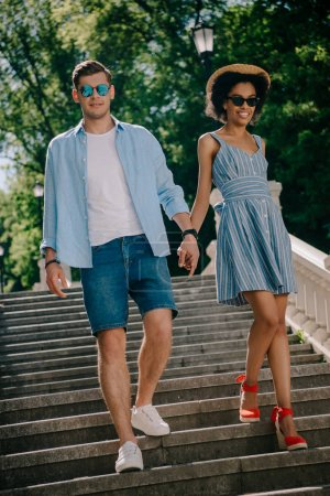 young stylish couple in sunglasses holding hands and going downstairs in park