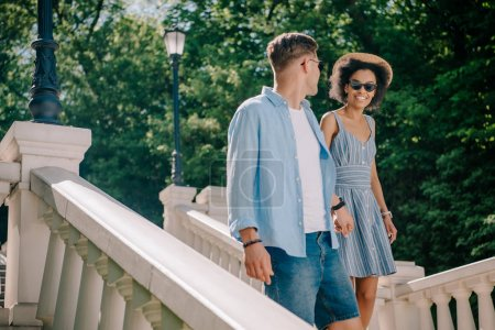 stylish interracial couple in sunglasses going downstairs in park